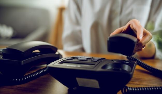 Feche a mão segurando um telefone fixo preto sobre a mesa no escritório.