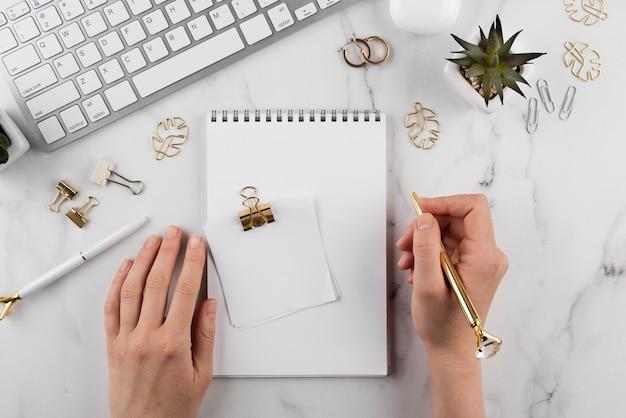 Feche a mão segurando uma caneta dourada