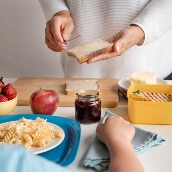 Feche a mão segurando uma fatia de pão