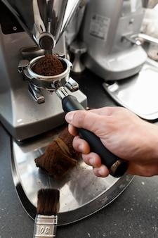 Feche a mão segurando uma ferramenta para fazer café