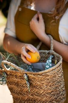 Feche a mão segurando uma laranja