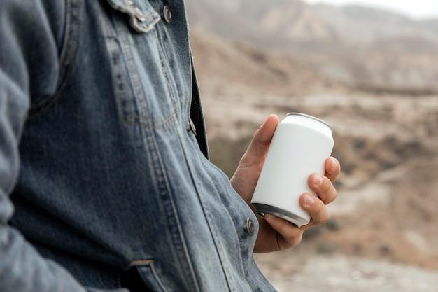 Feche a mão segurando uma lata de refrigerante