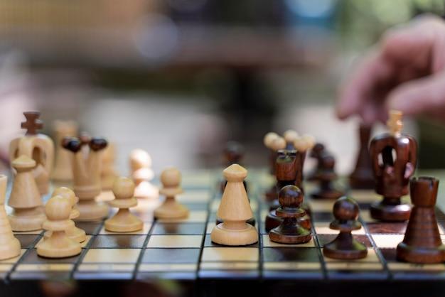 Feche a mão segurando uma peça de xadrez