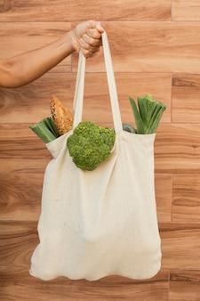 Feche a mão segurando uma sacola com vegetais