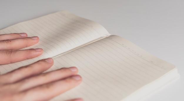 Feche a mão segure a nota vazia em branco na mesa branca b