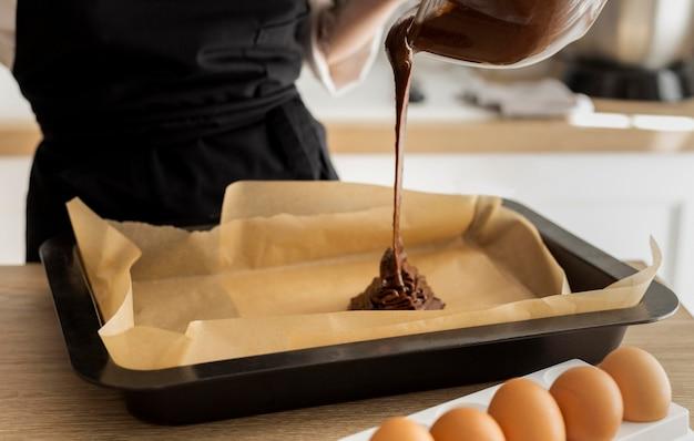 Feche a mão servindo chocolate