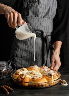 Feche a mão servindo creme na sobremesa