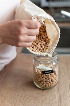 Feche a mão servindo grão-de-bico da sacola