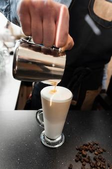 Feche a mão servindo leite no café