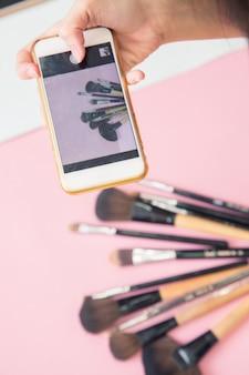 Feche a mão, tire uma foto por telefone de produtos de maquiagem e pincéis em fundo colorido