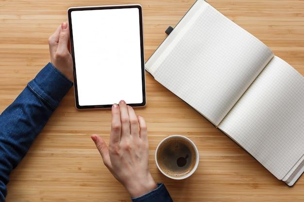 Feche a mão usando a tela branca do tablet e livro de nota na mesa do espaço de trabalho, coffee-break.