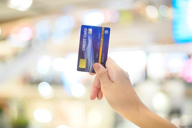 Feche a mão usando cartão de crédito no shopping