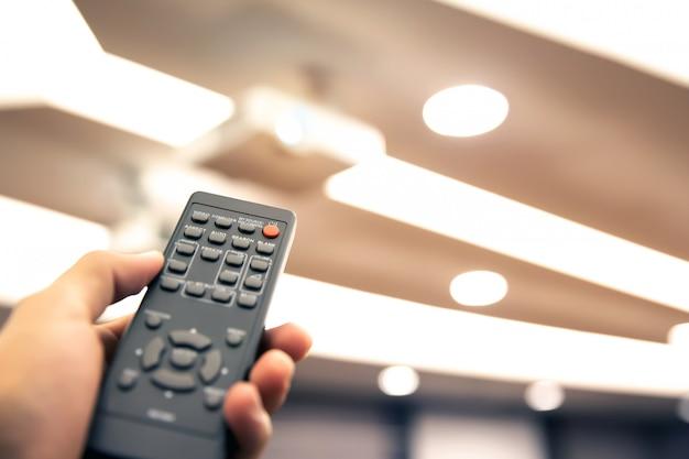 Feche a mão usando o controle remoto para ligar o retroprojetor na sala de reuniões ou na diretoria.