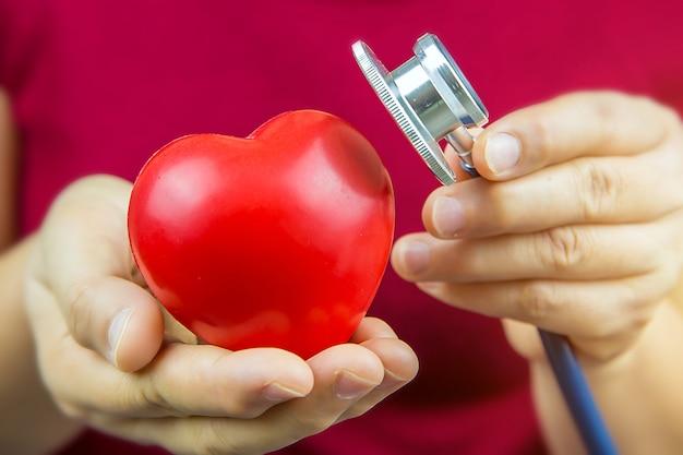 Feche a mão usando o estetoscópio para verificar um coração.