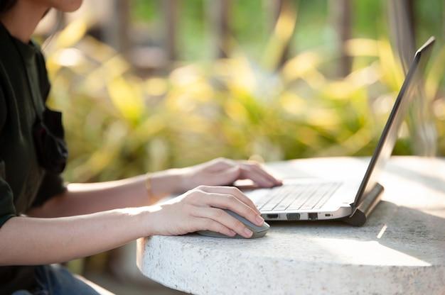 Feche a mão usando o mouse e o notebook trabalhando em casa