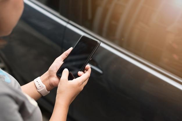 Feche a mão usando o smartphone perto de um carro em foco seletivo, conceito: desbloquear o carro com sm