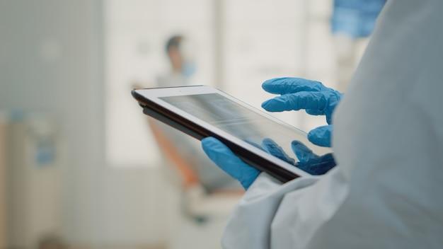 Feche a mão usando um raio-x odontológico em um tablet moderno
