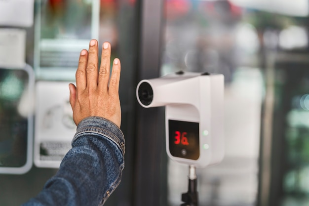 Feche a mão verificando a temperatura antes de entrar na loja por um infravermelho automático