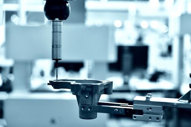 Feche a máquina de medição automática de coordenadas (cmm) para inspeção de peças de alta precisão durante o trabalho, tom azul
