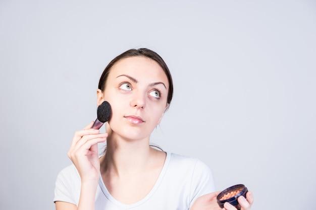 Feche a menina pensativa, aplicando maquiagem em pó no rosto usando um pincel enquanto olha para cima em um fundo cinza.