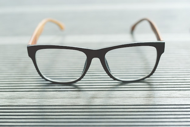 Feche a moda de óculos na mesa de madeira cor cinza.