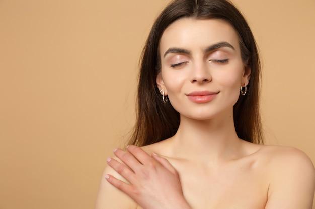 Feche a morena seminua mulher 20 anos com pele perfeita mão no ombro isolado no retrato de parede bege pastel. conceito de procedimentos cosméticos de saúde de cuidados com a pele.