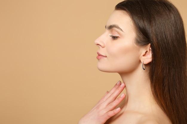 Feche a morena seminua mulher de 20 anos com a pele perfeita, mão no pescoço isolada na parede bege pastel, retrato. conceito de procedimentos cosméticos de saúde de cuidados com a pele.