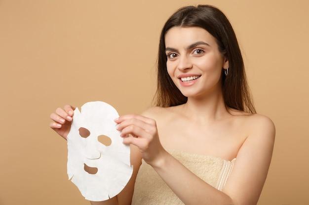Feche a morena seminua mulher de 20 anos com a pele perfeita, maquiagem nude isolada na parede bege pastel, retrato. conceito de procedimentos cosméticos de saúde de cuidados com a pele.