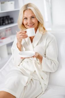 Feche a mulher branca sênior, sorrindo em roupão branco, segurando o chá no salão de esteticista.