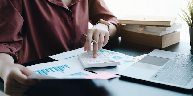 Feche a mulher de negócios usando a calculadora e verificando um gráfico em uma mesa de madeira no escritório