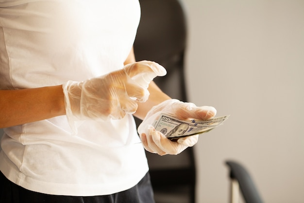 Feche a mulher desinfetar dinheiro com anti-séptico.