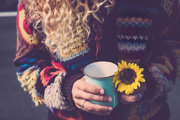 Feche a mulher loira hippie indie com uma xícara de chá ou café e flor do sol disponível - conceito de estilo de vida alternativo de liberdade para o desejo de viajar e as pessoas adoram sentir e viver a natureza e o mundo