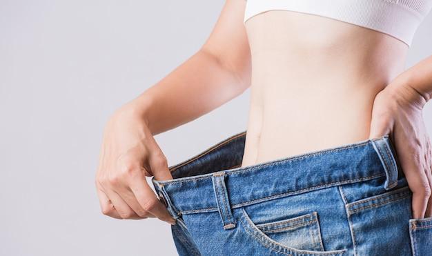 Feche a mulher magra, medindo sua cintura fina. saúde e conceito de estilo de vida da dieta da mulher para reduzir a barriga e moldar o músculo do estômago saudável.