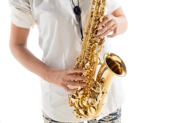Feche a mulher tocando saxofone isolado no fundo branco do estúdio. músico inspirado, detalhes da ocupação artística, instrumento clássico mundial para jazz e blues. conceito de hobby, criatividade.