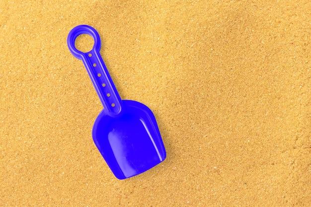 Feche a pá de areia azul vista isolada na praia de areia. adicionado espaço de cópia para texto.