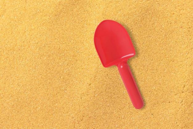 Feche a pá de areia vermelha vista isolada na praia de areia. adicionado espaço de cópia para texto.