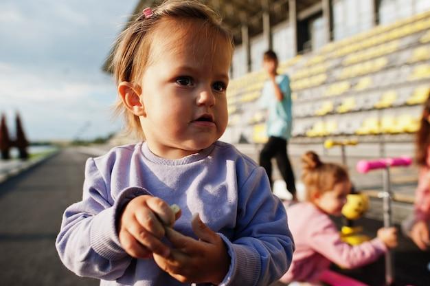 Feche a pequena menina em traje esporte roxo. a família de esportes passa o tempo livre ao ar livre com patinetes e patins.