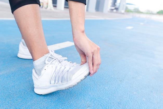 Feche a perna de uma mulher fazendo exercícios de alongamento na pista de corrida.