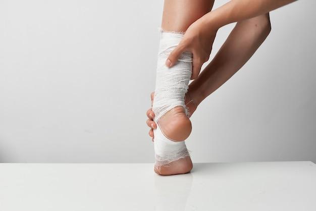 Feche a perna ferida de uma mulher com curativo