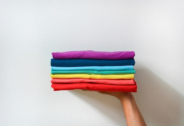 Feche a pilha de camisetas dobradas multicoloridas na mão