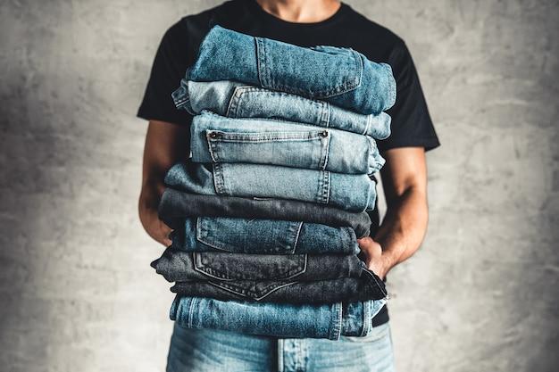 Feche a pilha de jeans azul dobrado na mão sobre a parede cinza