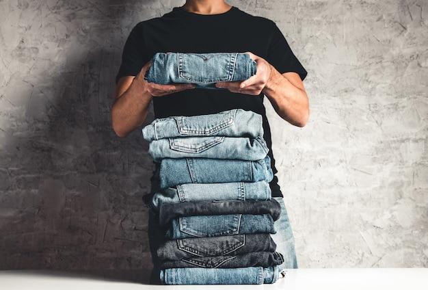 Feche a pilha de jeans azul dobrado na mão sobre o fundo cinza da parede, copie o espaço