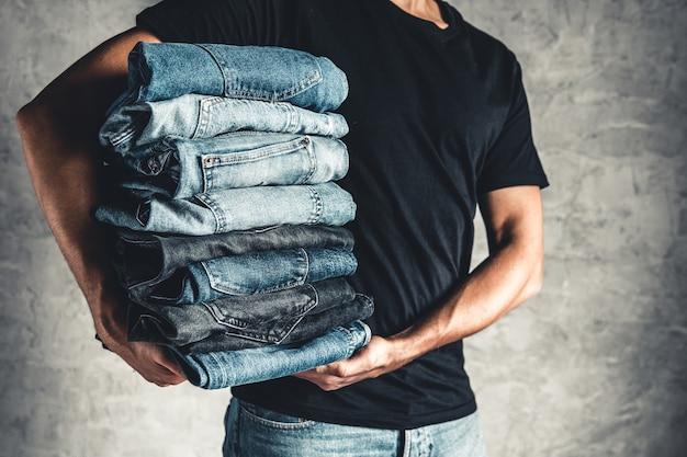 Feche a pilha de jeans azul dobrado sobre o fundo cinza da parede, copie o espaço