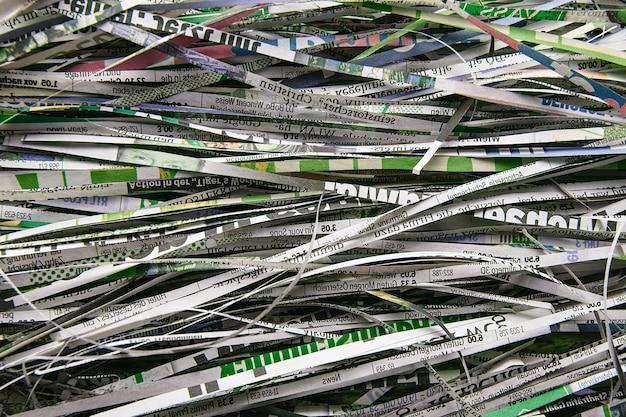 Feche a pilha de pedaços de papel do cortador de papel para segundo plano. reciclagem de papel para o destruidor. o conceito de reciclagem de matérias-primas e proteção ambiental
