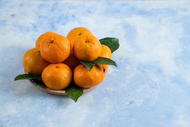 Feche a pilha de tangerinas com folhas