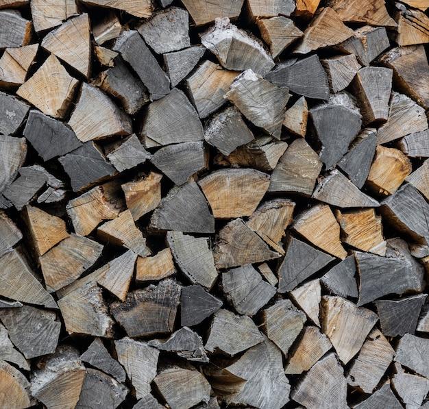 Feche a pilha de toras de madeira de carvalho secas, picadas, divididas e organizadas em uma pilha para o estoque de combustível de inverno, ângulo baixo, vista lateral