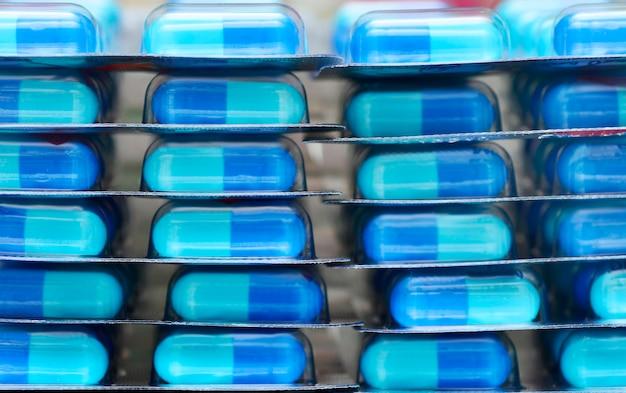 Feche a pilha de uma embalagem blister de cápsulas azuis