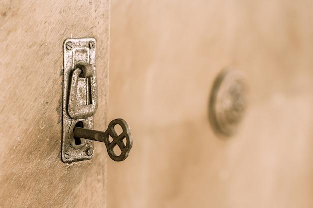 Feche a porta velha com a velha fechadura e a chave. chave velha e enferrujada dentro de um buraco de fechadura. foco seletivo na chave