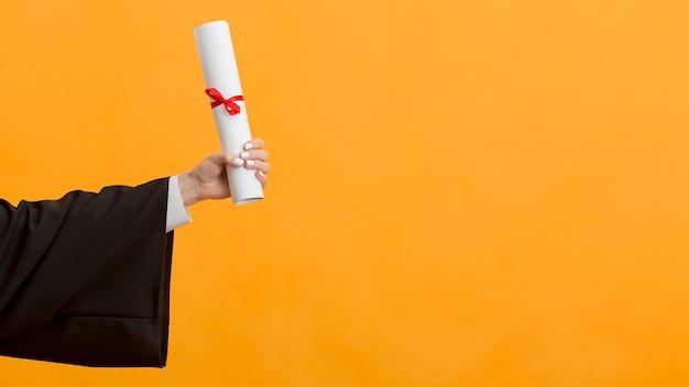 Feche a pós-graduação segurando um diploma