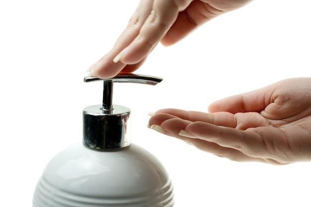 Feche a pressão da mão de uma mulher, bombeando a loção da garrafa e um sabonete líquido
